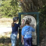 Girl Scouts cleaning netrance sign.